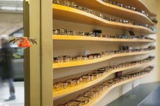 Geschwungenes Holzregal mit Brillen in Brillengeschäft in Berlin-Mitte
